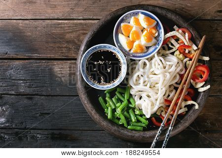 Ingredients for cooking stir fry udon noodles, green beans, sliced paprika, boiled eggs, soy sauce with sesame seeds in traditional bowls with wooden chopsticks over old wooden background. Flat lay