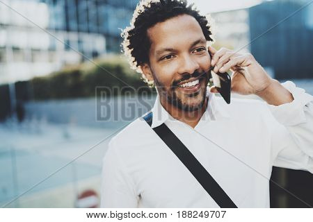 Smiling American African man using smartphone to call friends at sunny street.Concept of happy young handsome people enjoying gadgets outdoors.Blurred background