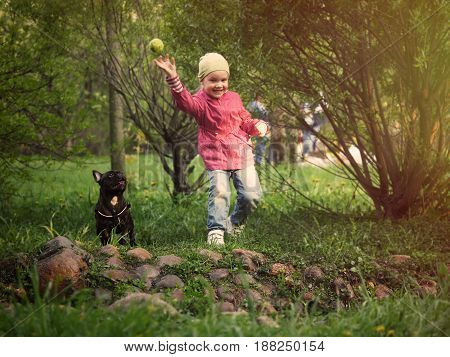 A small child plays with a dog. Fast girl running in the Park. The ball flies