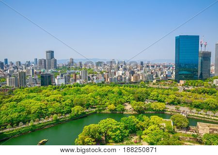 Aerial view of moat around castle park, Osaka business district and spectacular mountains surrounding the city from Osaka Castle, one of the most famous landmarks of Japan and Osaka.