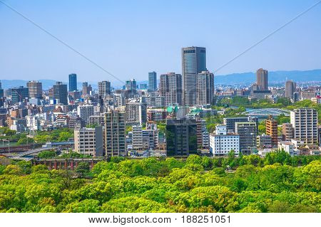 Panoramic view of Osaka business district and mountains surrounding the Osaka city. Beautiful aerial and garden view from Osaka Castle, one of the most famous landmarks of Japan. Spring time.