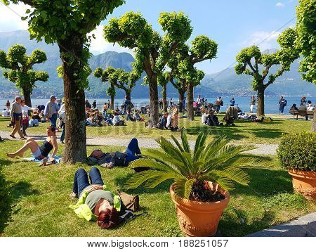 People Lying On The Grass By The Lake
