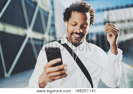 Attractive american african black man listening to music with headphones in urban background. Happy men using smartphone outdoors.Flares effects, blurred background