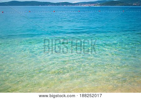 Sea bottom on the background of a hill range with many small houses a line of buoys and azure transparent blue sea. Blue cloudless sky. Zadar Croatia