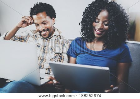Happy african american couple relaxing together on the sofa.Young black man and his girlfriend using modern laptops at home in the living room. Horizontal, blurred background.Front view.