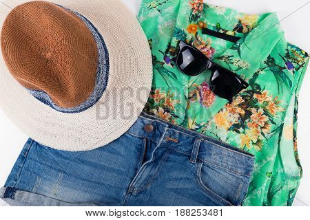 womens summer outfit. shirt, shorts, hat and sunglasses. top view