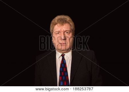 The serious senior businessman looking at camera isolated on black studio background. Concept of business
