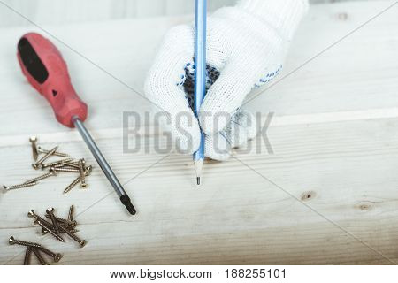 Hand with a pencil draws a marking to twist the screw with a screwdriver.