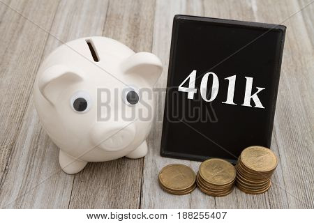 Saving for your retirement A piggy bank with retro freestanding chalkboard with gold coins on weathered wood with text 401k