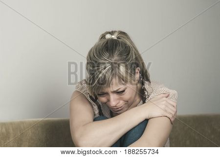 Woman Suffering From Depression Sitting On Bed And Crying.