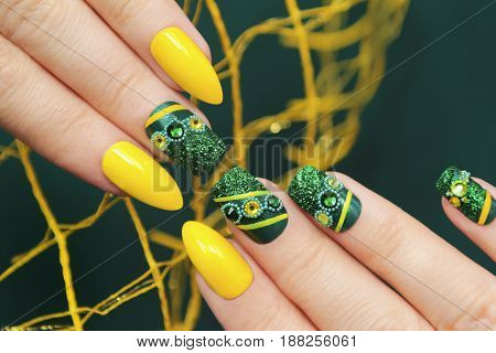 Green manicure on square the acute form of the nails with glitter,rhinestones and yellow lines a close-up.