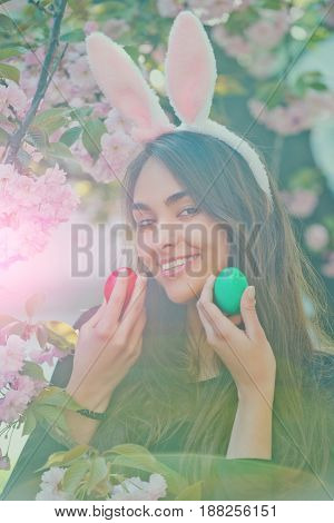 woman smiling with colored eggs green and red rosy bunny ears and long brunette hair at tree with blossoming sakura flowers on sunny day on floral environment. Easter. Spring