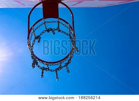 Outdoor basketball hoop with blue sky at sunny day