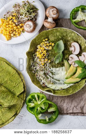 Green spinach matcha tortilla with vegan ingredients for filling. Sweet corn, avocado, green paprika, sprouts, mushrooms served in white plate over gray texture background and textile. Flat lay