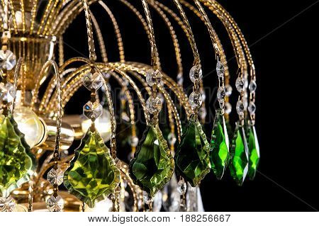 Chandelier for interior of the living room. chandelier details decorated with green crystals isolated on black background. Close-up photo