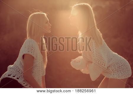 Homosexual couple of twin sexy girls or pretty women stylish models with long blond hair in fashionable white sweaters flirting on sunny day on natural background.