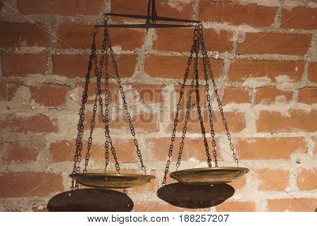 Gold justice scale backlit on brick background.