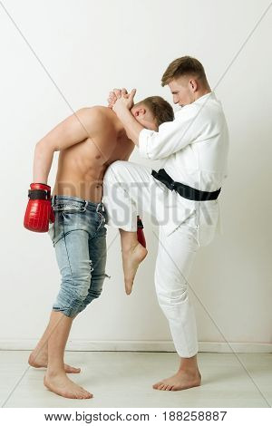 Men Fighting In Karate Kimono And Boxing Gloves