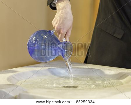 Pouring Water into Baptismal Font close up.