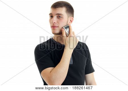 young charming guy turned his head to the side and shaves a beard trimmer is isolated on a white background close-up