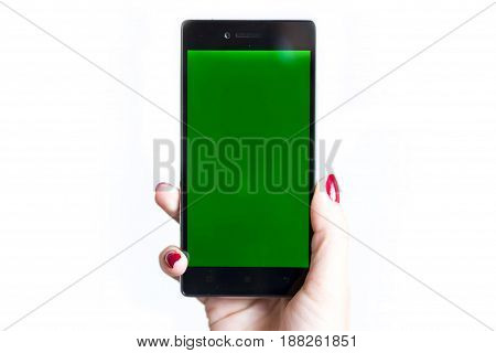 Young woman types and slides on her smartphone isolated on a white background. Cellphone with chroma key screen - green screen. Red nail polish fingers.