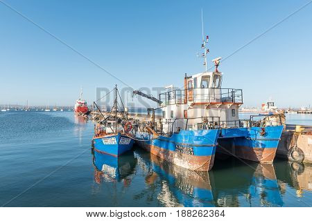 SALDANHA BAY SOUTH AFRICA - APRIL 1 2017: Ships at sunset at a pier in Saldanha Bay a town in the Western Cape Province