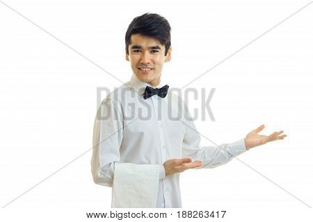 attractive young waiter smiles keeps a napkin and holds out his hand toward the isolated on white background