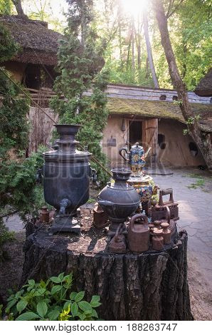 Traditional Russian samovars and old iron  as an outdoor decoration element outside an old building .