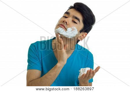 wonderful young guy with black hair tilted head and shaving foam on face isolated on white background