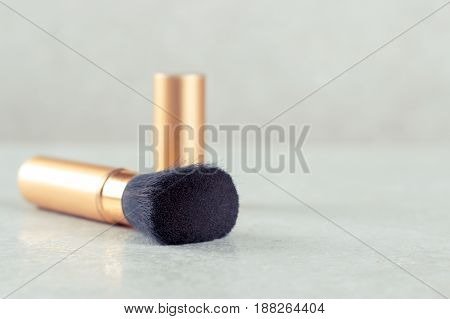 Cosmetic brush for applying make-up portable with a cap.
