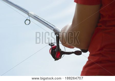 Fisherman catches a fish. Hands of a fisherman with a spinning rod in hand closeup. Spin fishing reel