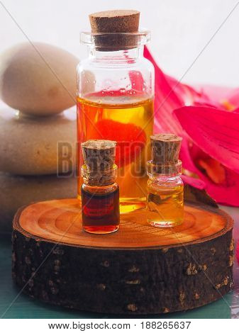 bottle of aroma essential oil or spa and natural fragrance oil with dry flower on wooden table image for aroma spa alternative therapy medicine and meditation aroma concept.