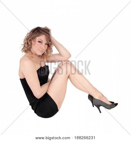 A beautiful young Caucasian woman crouching on the floor in jeans and black sweater isolated for white background.