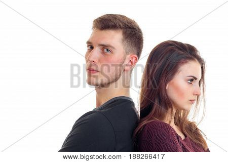 young guy and girl stand backs to each other and are angry is isolated on a white background close-up