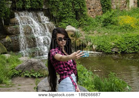 On the background of a waterfall girl with very long hair in sunglasses does selfie phone