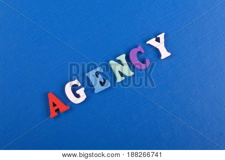 AGENCY word on blue background composed from colorful abc alphabet block wooden letters, copy space for ad text. Learning english concept