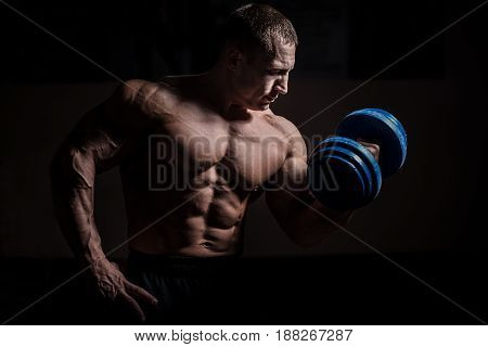Muscular bodybuilder guy doing exercises with dumbbell over black background