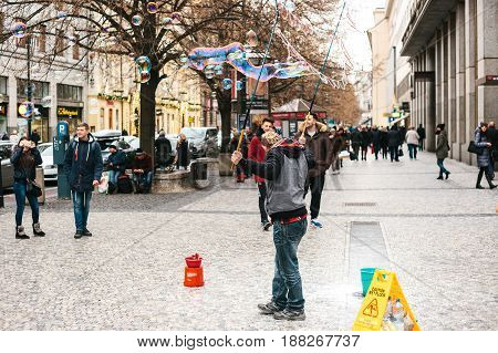 Prague, Czech Republic, December 24, 2016: The artist shows a performance with soap bubbles for tourists on the street in Prague. Entertainment of tourists in Christmas Europe.