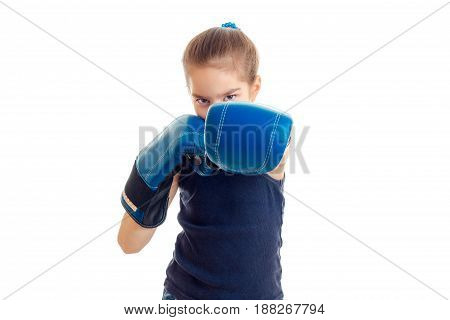 little girl in boxing gloves practicing by punch isolated on white background