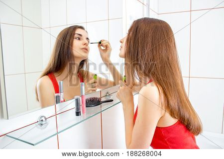 young beautiful brunette in red vest makes makeup in the bathroom