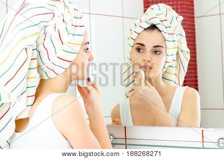 young beautiful girl with towel on head washes away make-up in the bathroom