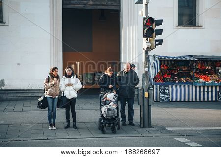 Munich, Germany, December 29, 2016: People stand at the traffic lights and are ready to cross the road. Everyday routine life in Germany.