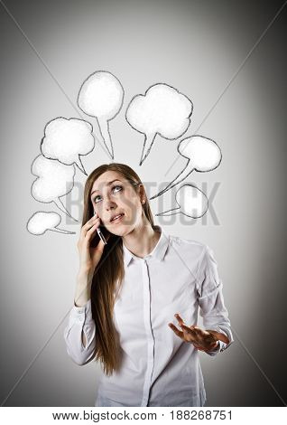 Woman in white is using a mobile phone with blank speech bubbles over her head.
