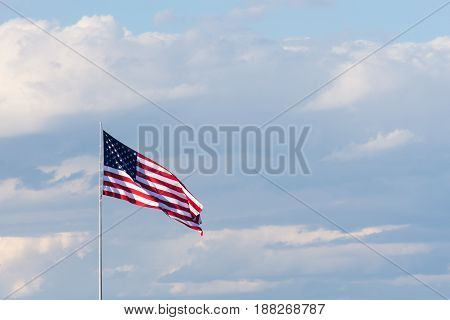 American flag unfurled in the breeze against a light blue sky with fluffy gray and white cumulus clouds.