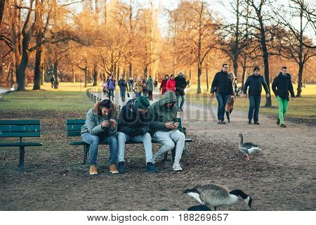 Munich, Germany, December 29, 2016: Friends sit on a bench in the English Garden in Munich one of the largest city parks in the world . Camping, communication, friendship, excellent pastime, networking.