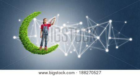 Cute kid girl standing on green moon throwing paper plane