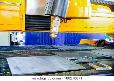 CNC plasma cutting machine for metal sheet. The head of a plasma torch is set to start.