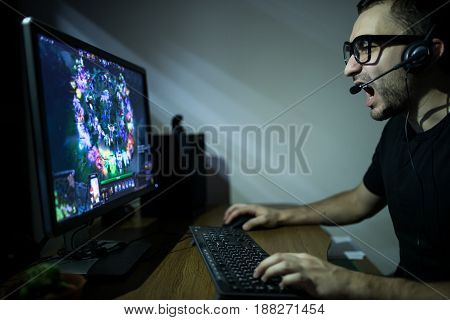 Young Gamer In Headphones And Glasses Using Computer For Playing Game At Home In The Night