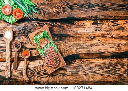 Roasted beaf steaks sliced and served on wooden board. Burned rustic wood background with vegetable and spices. Top view