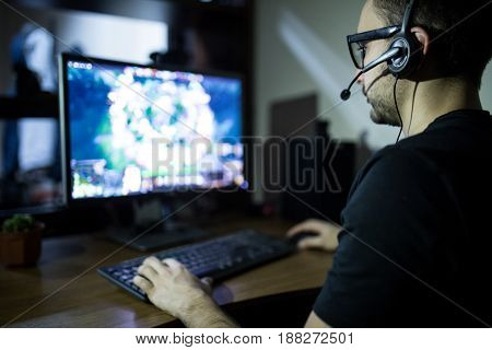Night Play. Young Gamer In Headphones And Glasses Using Computer For Playing Game At Home